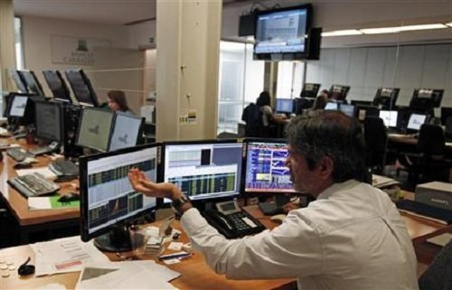 Trader gestures while watching screens in a trading room in Lisbon