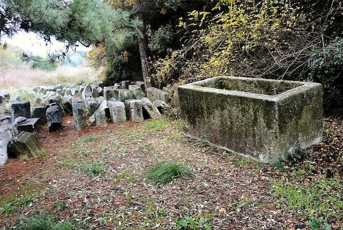 Figure 4. An empty sarcophagus kept next to the stones salvaged from the lion monument at Amphipolis