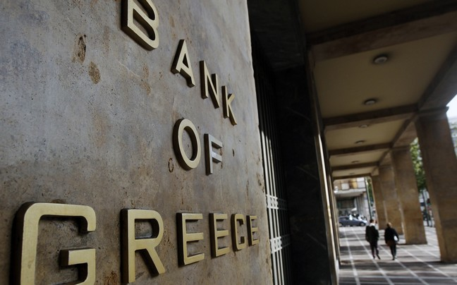 Pedestrians walk past the bank of Greece in Athen