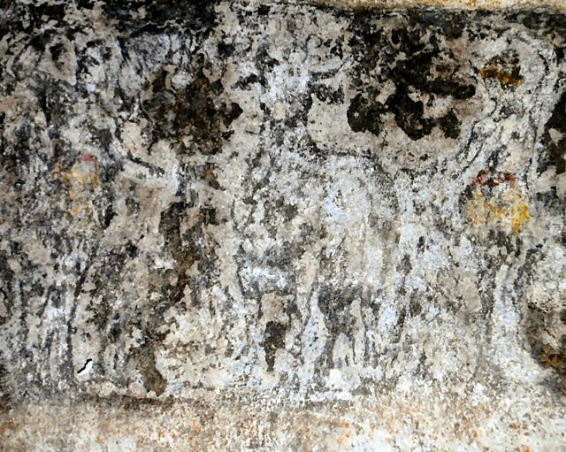 A man (left) and woman (right) wearing red belts and dancing either side of a sacrificial bull (centre) in a painting discovered in the Amphipolis tomb