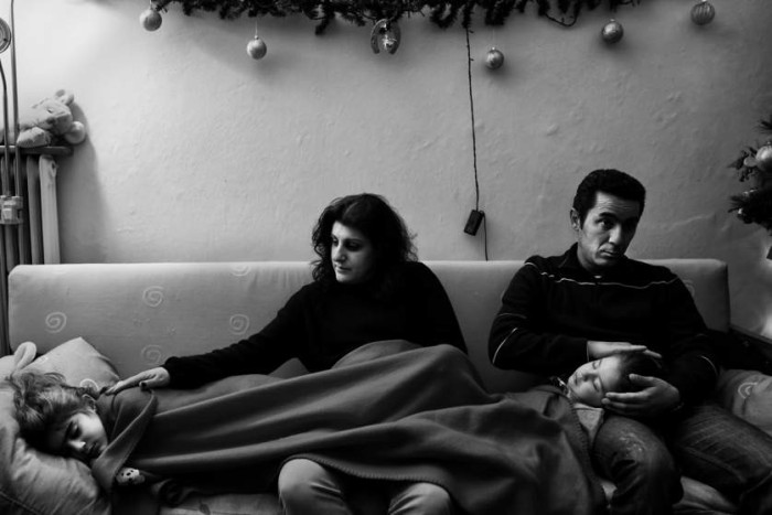Photo by Angelos Tzortzinis (Matina Tetsiou, her husband Lenos Aspros and their children rest in their living room at the district of Nea Ionia. Matina and Lenos are both unemployed for the past year)