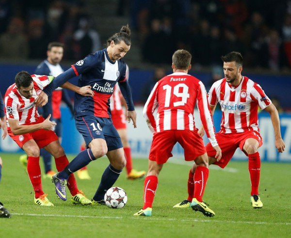 PSG's Zlatan Ibrahimovic, 2nd left, challenges for the ball with Olympiakos' players David Fuster, 2nd right, and Olympiacos' Andreas Samaris, right, during the Group C Champions League soccer match between Paris Saint Germain and Olympiakos FC at the Parc des Princes stadium in Paris, France, Wednesday, Nov. 27, 2013. Unindentified Olympiakos player at left. (AP Photo/Francois Mori)