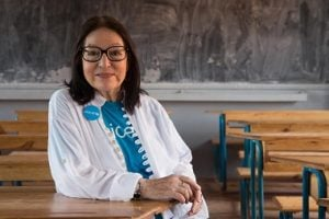 On 26 February, UNICEF Goodwill Ambassador Nana Mouskouri, seated at a student's desk in a classroom, smiles during her visit to a public primary school in Ampangabe Village in Analamanga Region. From 24 to 28 February 2015, internationally acclaimed singer, humanitarian and UNICEF Goodwill Ambassador Nana Mouskouri visited Madagascar to review UNICEF-supported programmes and to draw added attention to the considerable challenges and constraints faced by the country's vulnerable children and families. Madagascar is slowly emerging from a protracted and debilitating political crisis and the ensuing economic decline. The country remains one of the world's poorest: 91 per cent of the population live on less than US $2.00 a day, and many of the poorest are children – who have been hardest hit in the crisis and live in extreme poverty. The crisis also resulted in a decrease in public investment in social sectors, weakening further the delivery of basic social services, as well as access to, and use of, these vital services. The health, education, and water, sanitation and hygiene (WASH) sectors have seen significant declines. Madagascar is ranked as the fourth-worst country in the world in terms of access to safe drinking water, and eight from last in access to sanitation. Only half of the overall population and 35 per cent of the rural population have access to improved water sources, with 38 per cent of people in rural areas relying on surface water for drinking; and just 14 per cent of the population has access to improved sanitation facilities. Nearly half (47 per cent) of all children under age 5 are stunted – the fourth-highest rate in the world; and maternal mortality remains very high, at 500 per 100,000 live births. The country is also no longer on track to achieve universal primary-school education. The net primary enrolment rate has decreased (from 83 per cent in 2005 to 69 per cent in 2012), and about 1.5 million school-age children are currently