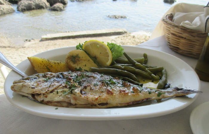Fish with vegetables and olive oil at a taverna by the sea in Crete