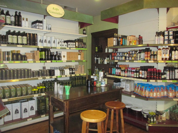 Olive oils and other products on the shelf at the Pantopoleion tis Mesogiakis Diatrofis, with a tasting table and stools in front of them