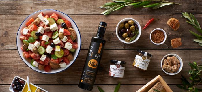 Kyklopas olive oil, olive paste, and olives next to a colorful salad