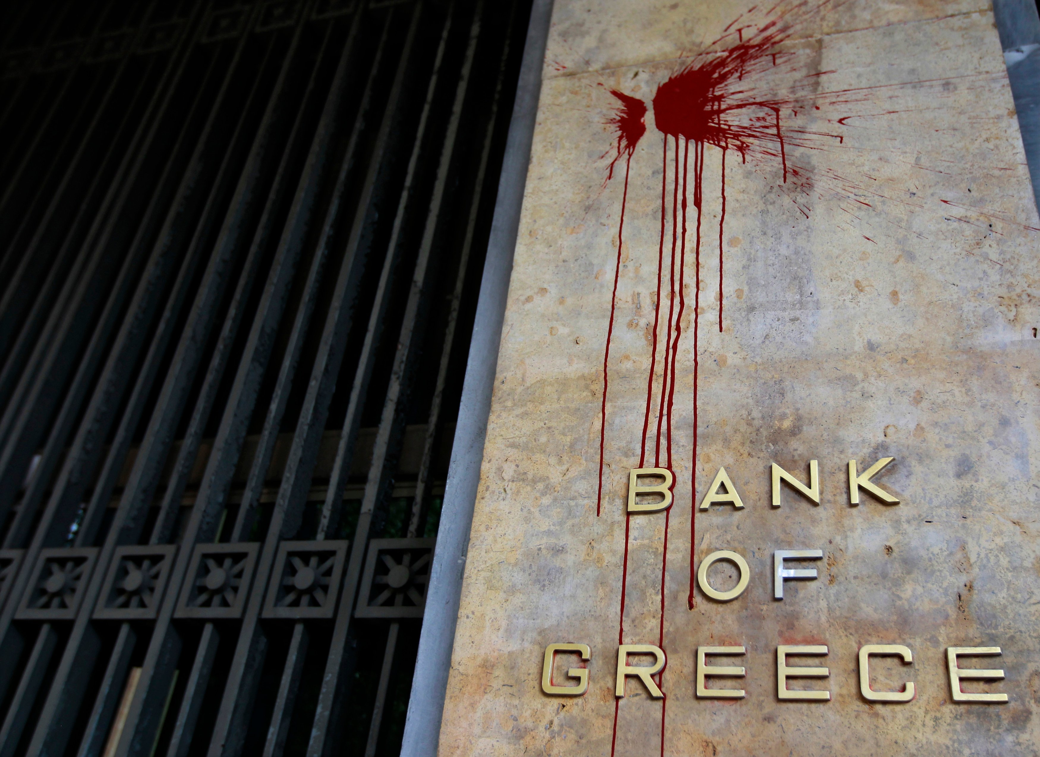 The defaced facade of the Bank of Greece is seen after a night of violence which followed the Greek parliament approval of a deeply unpopular austerity bill in Athens, February 13, 2012. As Greeks head back to the polls in an election that may help to decide whether they stay in Europe's common currency, and as Cypriot politicians move closer to asking for an international bailout - perhaps as early as this week - the story of Andreas Vgenopoulos and Marfin helps explain how Greece and Cyprus got here. Picture taken February 13, 2012. To match Special Report GREECE/MARFIN REUTERS/John Kolesidis (GREECE - Tags: BUSINESS EMPLOYMENT CIVIL UNREST POLITICS) - RTR33J61