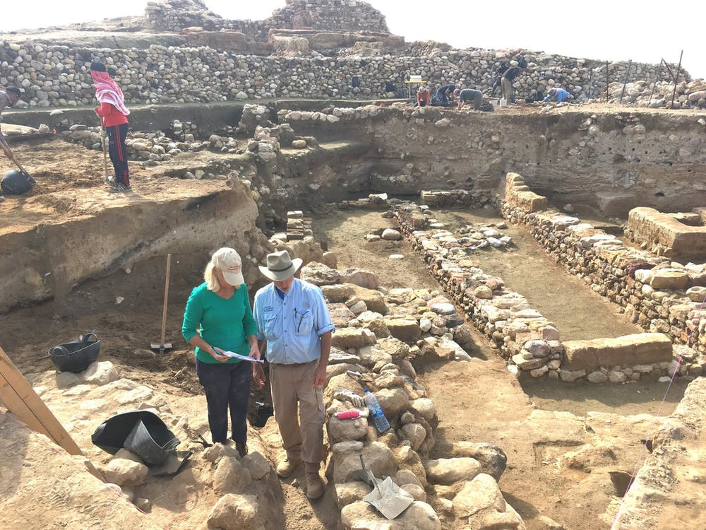 Researchers stand near the ruins of ancient city walls, with the destruction layer about midway down each exposed wall.